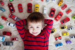 Förtjusande pojke som ligger på jordningen, leksakbilar runt om honom och att se Arkivfoton