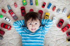 Förtjusande pojke som ligger på jordningen, leksakbilar runt om honom och att se Royaltyfria Foton
