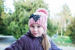 Förtjusande posera för liten flicka Bärande vinterlag och hatt Arkivfoto