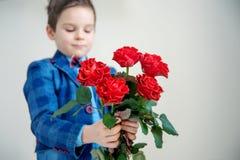 Förtjusande pys i dräkt med buketten av röda rosor på en ljus bakgrund fotografering för bildbyråer