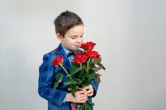Förtjusande pys i dräkt med buketten av röda rosor på en ljus bakgrund arkivfoto
