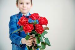 Förtjusande pys i dräkt med buketten av röda rosor på en ljus bakgrund royaltyfri bild