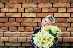Förtjusande pys med en bukett av tulpan Royaltyfria Bilder