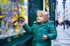 Förtjusande pys som ser till och med fönstret på juldecoen Royaltyfri Foto