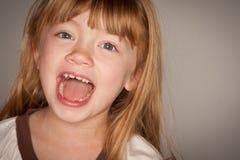 Förtjusande röd Haired flicka som skrattar på grå färger royaltyfri foto