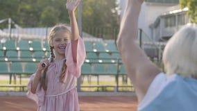 Förtjusande rolig flicka med två råttsvansar som står på tennisbanan som rymmer racket, den vinkande handen till farmodern och stock video