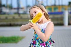 Förtjusande rolig flicka som äter havre på majskolven Arkivfoton