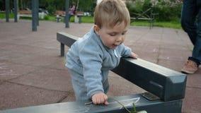 Förtjusande roligt behandla som ett barn lek på lekplatsen under omsorg av hans hipsterföräldrar lager videofilmer