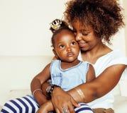 Förtjusande söt ung afro--amerikan moder med den gulliga lilla dottern och att hänga hemma och att ha gyckel som spelar att le arkivbild