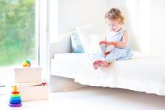 Förtjusande sammanträde för litet barnflickaläsebok på vit säng arkivbild