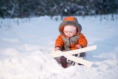 Förtjusande sitta barnvakt på snow med skidar 免版税库存照片