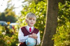 Förtjusande skolpojke med böcker och jordklotet på utomhus Utbildning för ungar tillbaka begreppsskola till Royaltyfri Fotografi