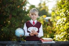 Förtjusande skolpojke med böcker och jordklotet på utomhus Utbildning för ungar tillbaka begreppsskola till Arkivfoton