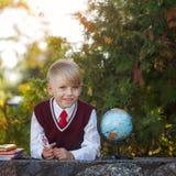 Förtjusande skolpojke med böcker och jordklotet på utomhus Utbildning F Royaltyfri Foto