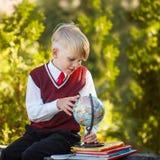 Förtjusande skolpojke med böcker och jordklotet på utomhus Utbildning F Arkivfoto