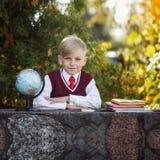 Förtjusande skolpojke med böcker och jordklotet på utomhus Utbildning F Royaltyfria Bilder