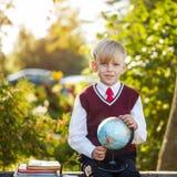 Förtjusande skolpojke med böcker och jordklotet på utomhus Utbildning F Arkivfoton