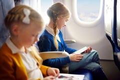Förtjusande små barn som reser vid ett flygplan Flickasammanträde vid flygplanfönstret och läsning hennes ebook under flyget Reso Arkivbild