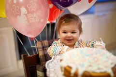 Förtjusande små behandla som ett barn flickan som firar den första födelsedagen Behandla som ett barn äta marshmellowsgarnering p Arkivfoto