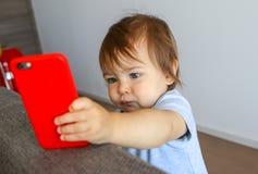 Förtjusande små behandla som ett barn pojken som allvarligt ser på skärmen av mobiltelefonen arkivfoton