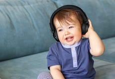 Förtjusande små behandla som ett barn pojken som hemma lyssnar till musik i hörlurar på hans head sammanträde på den blåa soffan arkivfoto