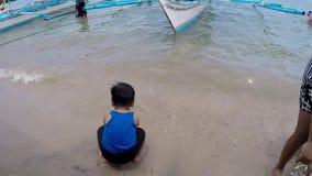 Förtjusande små behandla som ett barn pojken som spelar längsgående stödbjälke på den vita stranden lager videofilmer