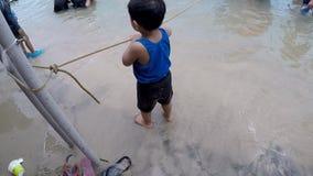 Förtjusande små behandla som ett barn pojken som spelar längsgående stödbjälke på den vita stranden arkivfilmer