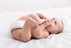 Förtjusande små behandla som ett barn suga foten som ligger på säng arkivbild