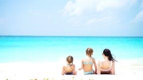Förtjusande små flickor och barnmoder på den vita stranden arkivfilmer