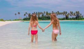Förtjusande små flickor på stranden under sommarsemester arkivbilder