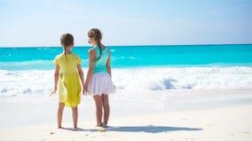 Förtjusande små flickor som går på stranden Den tillbaka sikten av ungar tycker om tillsammans havssikt lager videofilmer