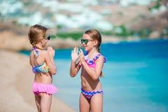 Förtjusande små flickor som har gyckel under strandsemester Att smälla sig på gömma i handflatan royaltyfri fotografi