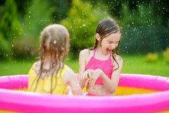 Förtjusande små flickor som spelar i uppblåsbar, behandla som ett barn pölen Lyckliga ungar som plaskar i färgrik trädgårds- lek, Royaltyfri Foto