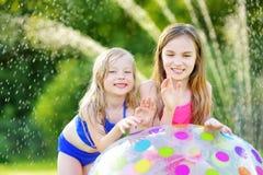 Förtjusande små flickor som spelar med den uppblåsbara strandbollen i en trädgård på solig sommardag Gulliga barn som har gyckel  royaltyfri bild