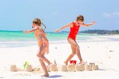 Förtjusande små flickor under sommarsemester Ungar som spelar med strandleksaker på den vita stranden Arkivbilder