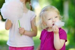 Förtjusande små systrar som äter godis-floss arkivfoto