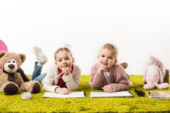 förtjusande små systrar som drar med färg, ritar tillsammans på golv royaltyfria foton