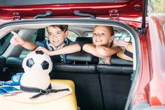 förtjusande små ungar, i att gå för bil arkivbild