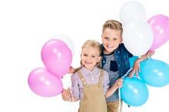 förtjusande små ungar som rymmer färgrika ballonger och ler på kameran Arkivfoton