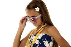 Förtjusande solbränd flicka som bär en tropisk klänning som spelar med hennes exponeringsglas Royaltyfri Fotografi