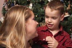 Förtjusande son som talar till mamman i Front Of Christmas Tree Royaltyfri Bild