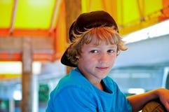 Förtjusande stående av den gulliga pojken med tillbaka hatten Arkivbild