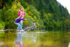 Förtjusande systrar som spelar vid Hallstatter, ser sjön i Österrike på varm sommardag Gulliga barn som har roligt plaskande vatt arkivbild