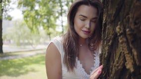 Förtjusande ung flicka för stående med långt brunetthår som bär ett långt vitt anseende för sommarmodeklänning bredvid ett träd arkivfilmer