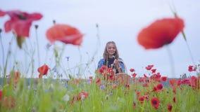 Förtjusande ung flicka som går i vallmofältet som samlar blommor i den vide- korgen Anslutning med naturen gr?n red lager videofilmer