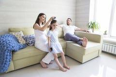 Förtjusande ung gravid familj i vardagsrum Lycka och lov royaltyfria bilder