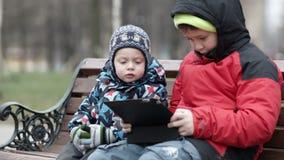 Förtjusande ung pojke som håller ögonen på hans broder stock video