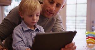 Förtjusande ung vit pojke som lär att använda minnestavladatoren Arkivfoto
