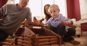 Förtjusande unga barn som bygger ett trähus med familjen royaltyfria foton