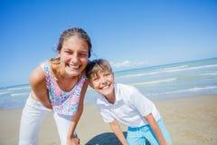 Förtjusande ungar har gyckel på stranden Royaltyfria Bilder